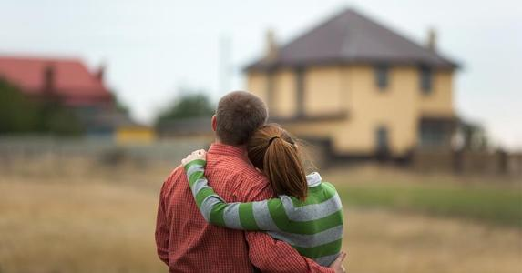 young-couple-hugging-eachother-looking-at-house-distance_573x300